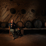 vernaccia wine producer in front of some barrels sipping his own treasure